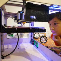 kid studying a 3D printer