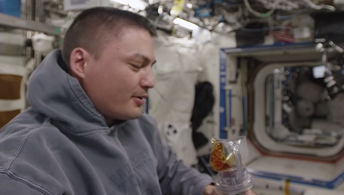 Astronaut Kjell Lindgren with the 3D printed device in the ISS