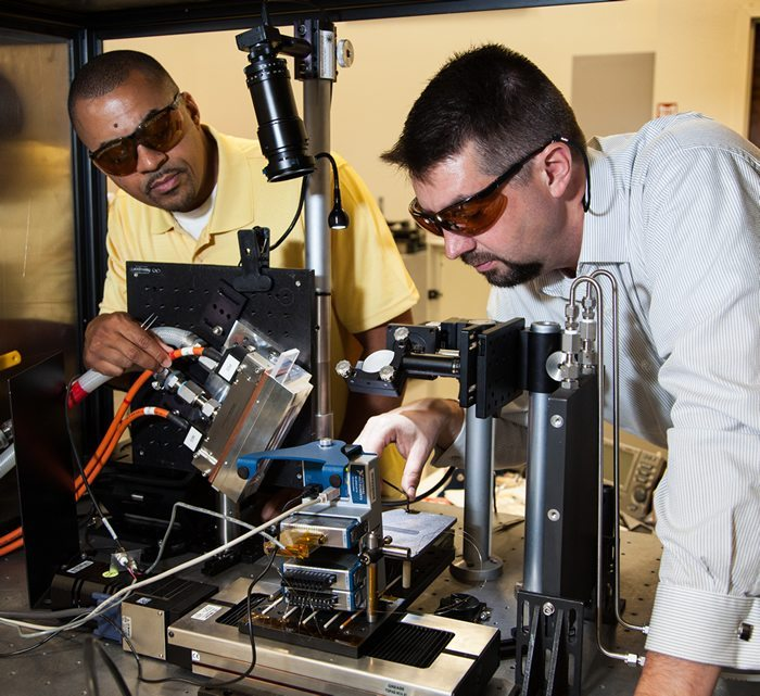 Ibo Matthews (left) adjusting a 4 KW laser. Image via.