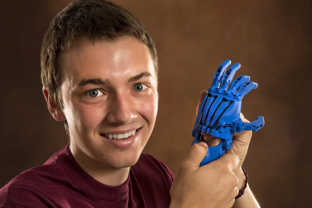 CMU engineering student Austin Brittain holds a prototype of a 3D printed hand he made. Central Michigan University photos by Steve Jessmore