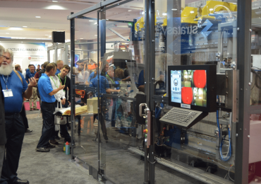 Dick Anderson (far left) watches the Stratasys Infinite Build in action at IMTS 2016. Photo by Michael Petch