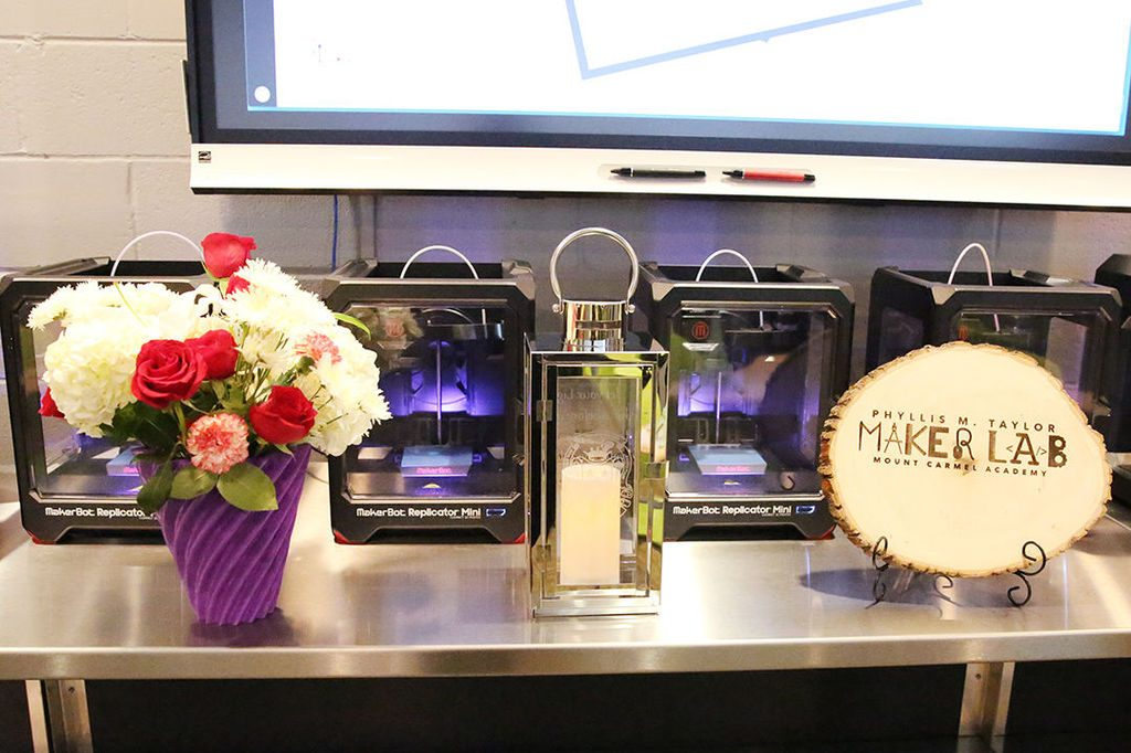 A 3D printed vase (left) and laser engraved plaque (right) presented to Phyllis M. Taylor and the Most Reverend Gregory Aymond, Archbishop of New Orleans at the opening of the new Maker Lab. Photo via: mcacubs.com