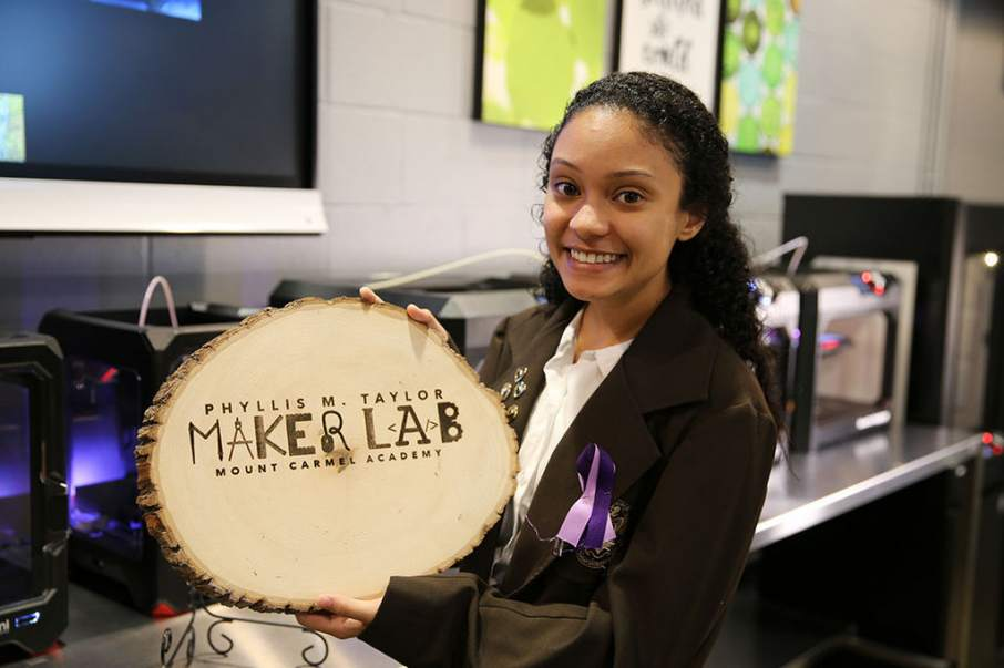 A student holds a laser engraved plaque to commemorate the opening of the Maker Lab. Photo via
