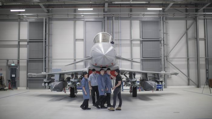 Engineering apprentices stand with BAE's Eurofighter typhoon warplane. Photo via: FinancialTimes