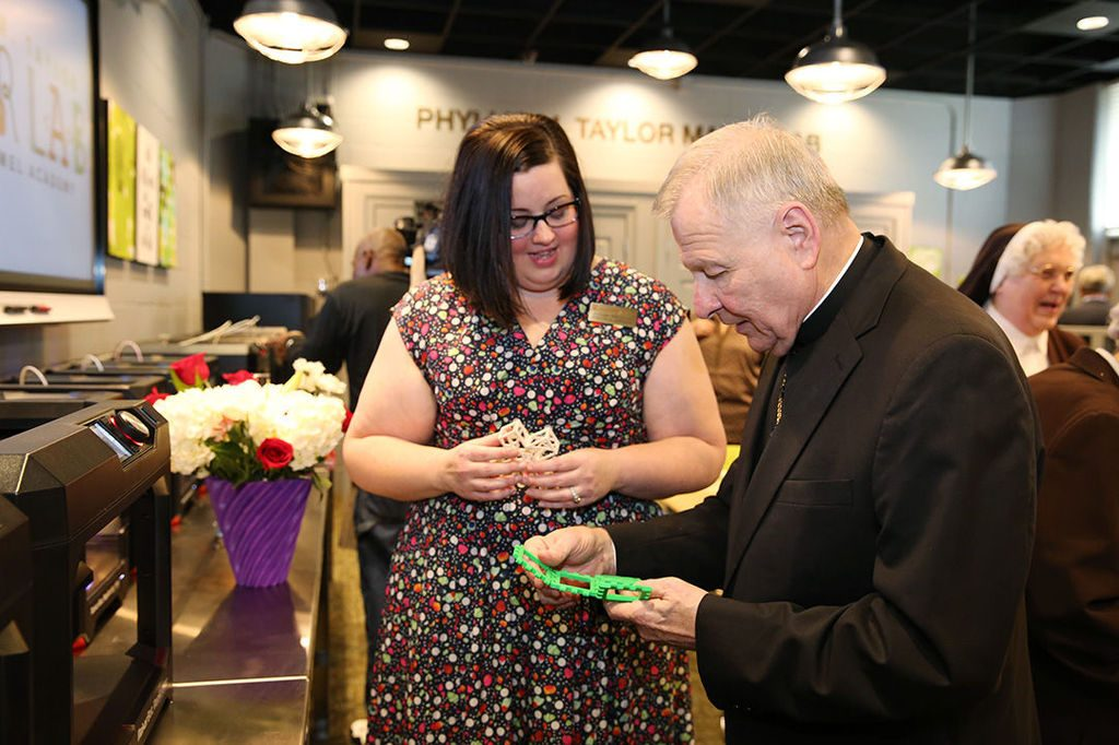 The Archbishop of New Orleans examines a 3D printed gift from Carmel students. Photo via: mcacubs.com