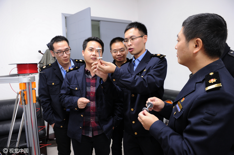 The engineers examining the 3D printed parts. Image via ChinaDaily.