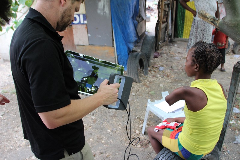 Danis' limb being scanned by Jeff Erenstone near her home in the Airport tent city. Photo via Enable Community Foundation.