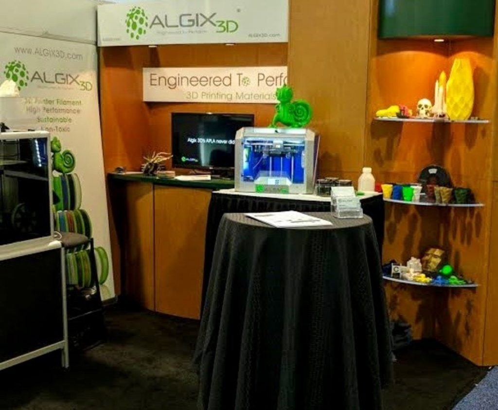 The ALGIX3D booth sporting the company's lime green chameleon mascot. Photo via: ALGIX3D
