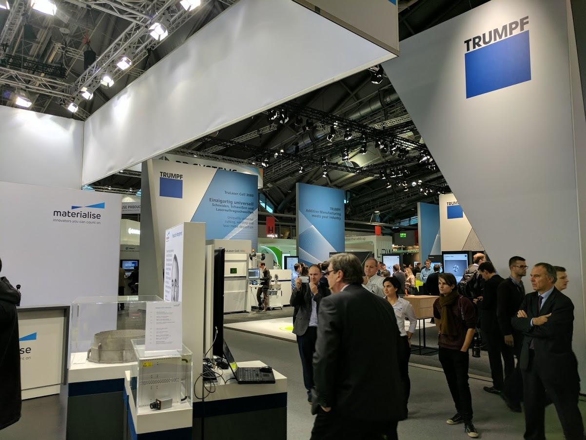Helmut Zeyn of Siemens Digital Factory Division presenting at Materialise booth during Formnext with Trumpf exhibiting opposite. Photo by Michael Petch.