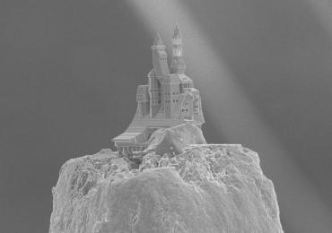 A traditional Russian Datsche castle 3D printed onto the tip a pencil. Photo via: Ovsianikov et al. Tu Wien