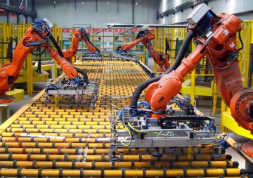 Robotic arms moving panes of glass for cars. Photo via: ICAPlants/Wikimedia Commons