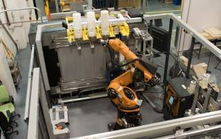 This robotic arm can refill the machine with more feedstock. Photo by Nick Miotke for CNET Roadshow.