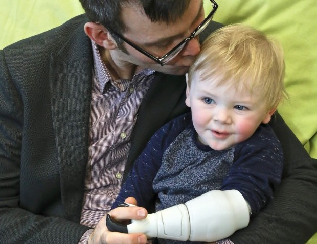 Ben Ryan and his 2 year old son Sol with a 3D printed prosthetic arm. Photo via Ben Ryan on Indiegogo