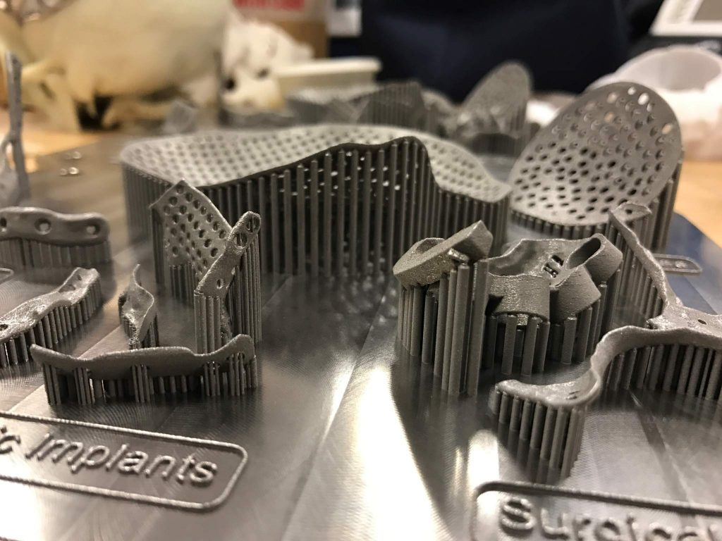 Finished additive manufactured titanium implants and surgical guides attached to build plate prior to post-processing. Photo via Renishaw.