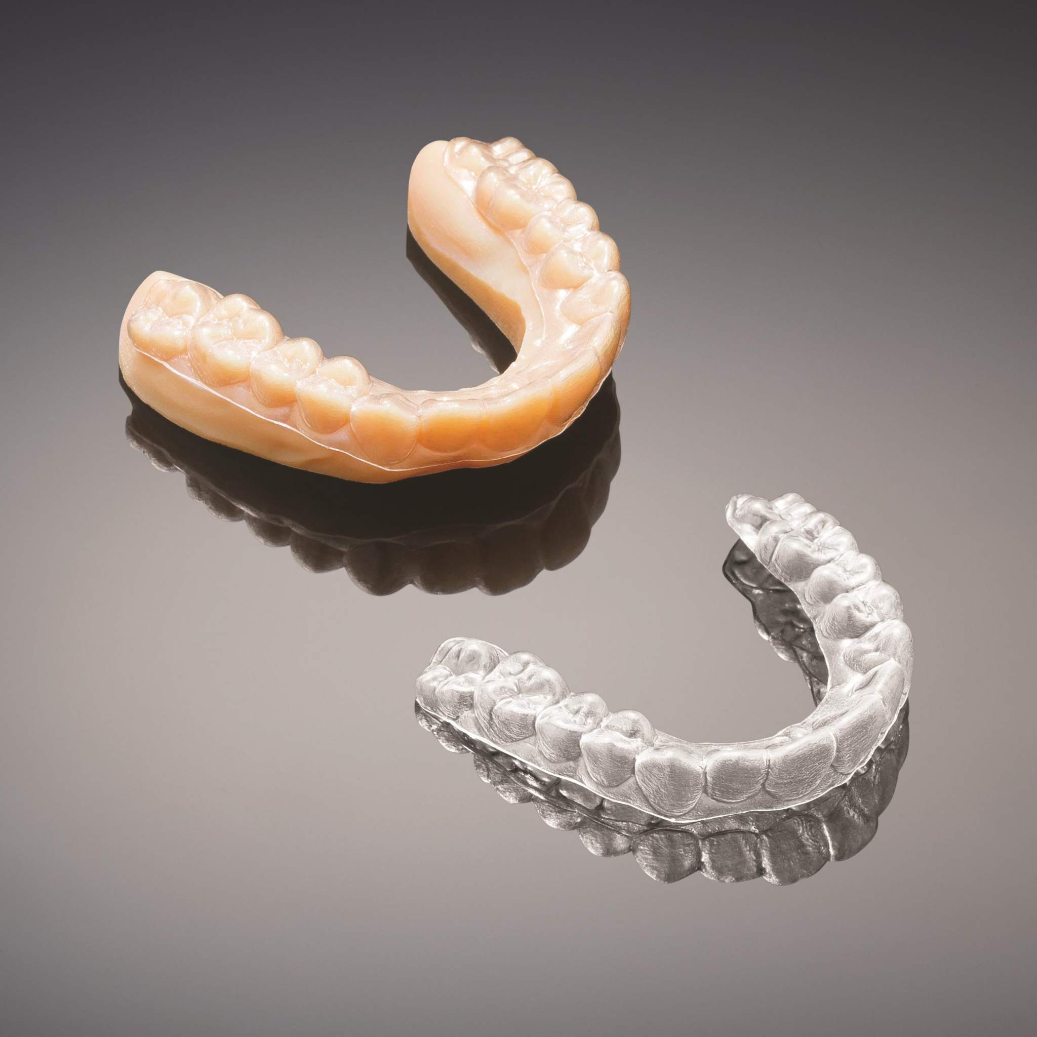 3D printed mold (upper left) and resulting aligner. Image via Stratasys.