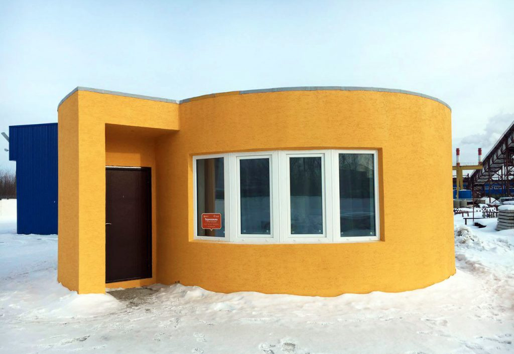 Exterior of the 3D printed, then painted Apis Cor house. Photo via Apis Cor