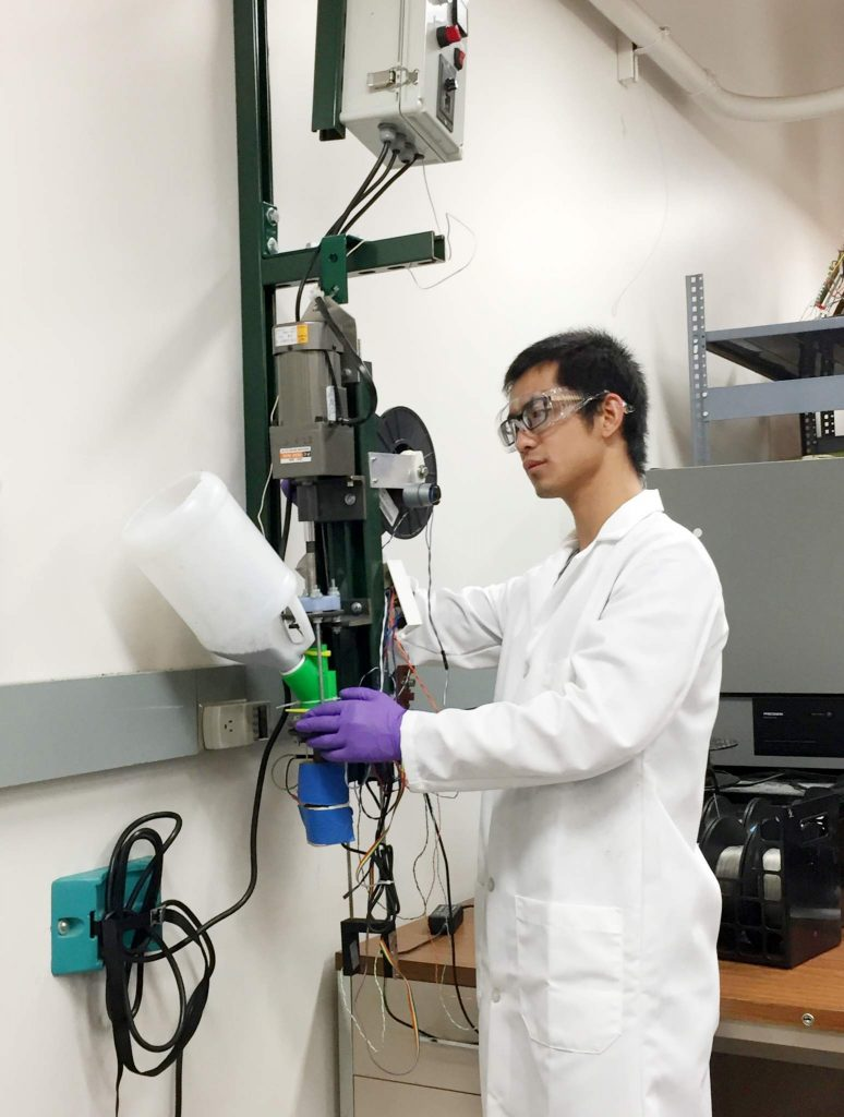 Michigan Tech graduate student adjusts a prototype vertical recyclebot used to turn waste plastic into 3-D printing filament. (Photo: S. Zhan, CC BY SA)