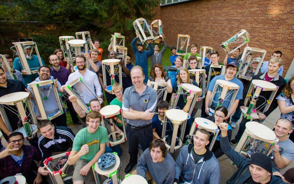 Michigan Tech students celebrate a massive delta-style 3D printer build as part of a class on Open Source 3D Printing. Professor Joshua Pearce seen center. Photo by S. Bird/MTU, CCBYSA