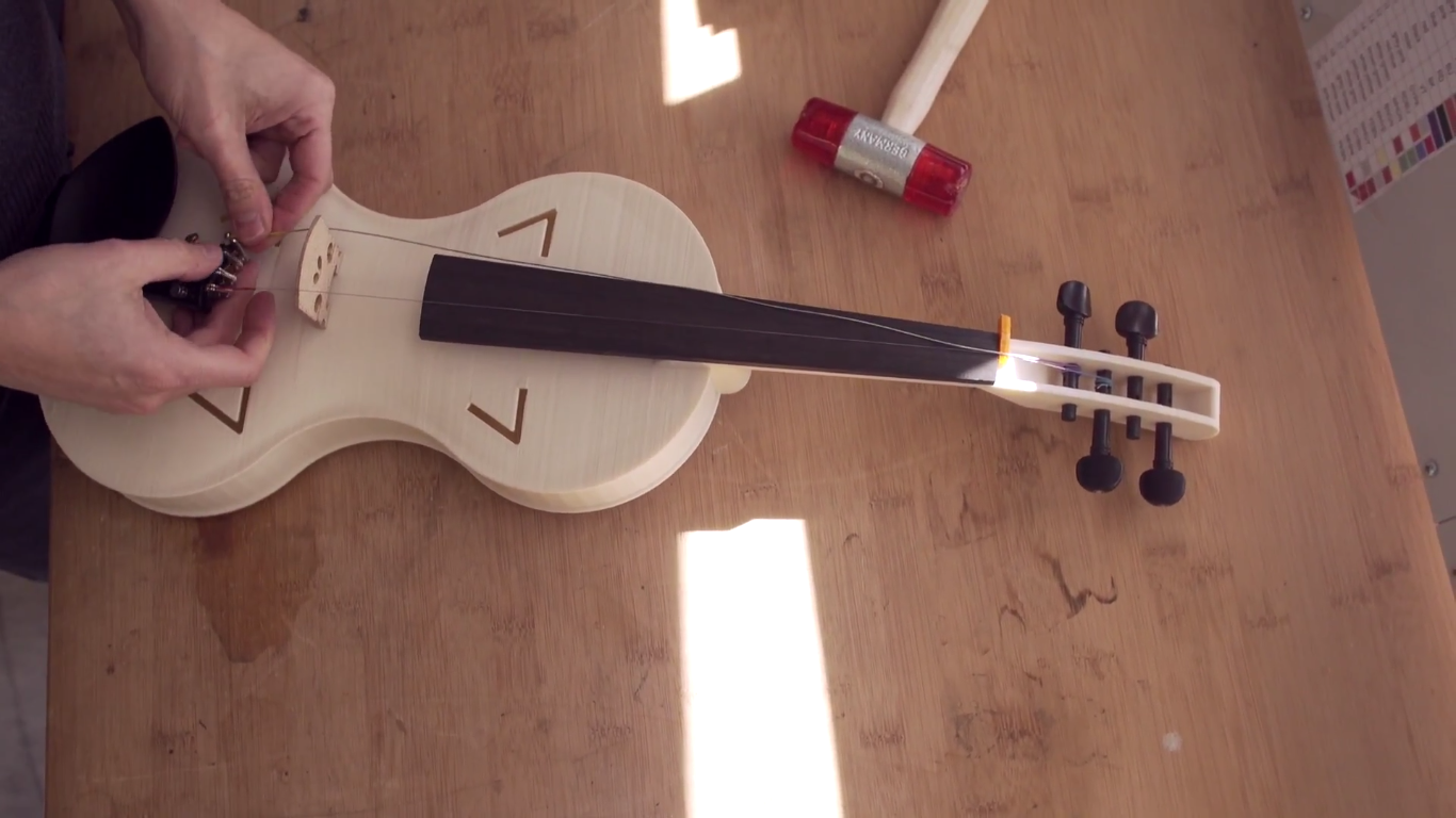 The strings being attached to the 3D printed violin by Ofer Lowinger. Photo via BigRep.