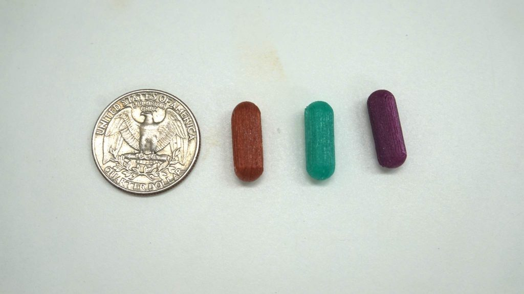 Colorful Printlet capsules with quarter for scale.