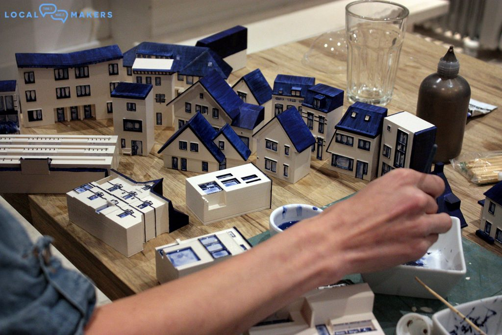 Finishing touches to the 3D printed houses. Photo via Local Makers