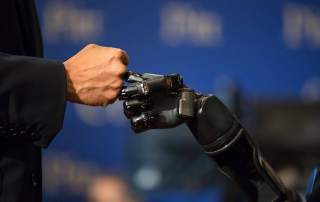 DARPA robotic arm fist bump. Photo via DARPA on Facebook