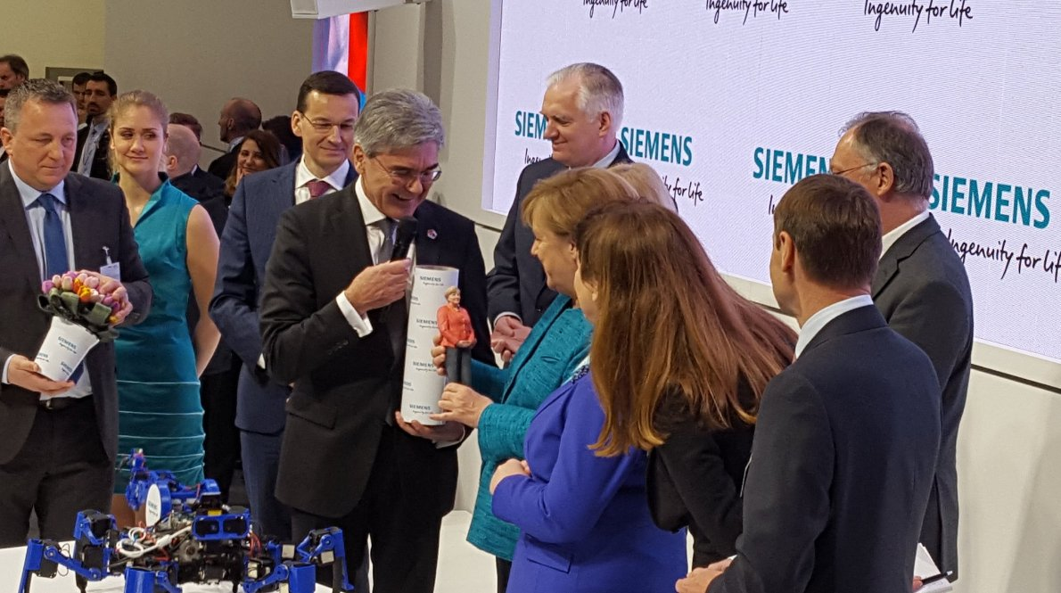 Siemens CEO, Joe Kaeser presenting Angela Merkel today with a 3D printed figure of the Chancellor. Photo via Siemens.