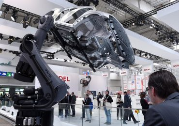 A KUKA robotic arm lifts the body of a car at Hannover Messe 2017. Photo via @hannover_messe on Twitter