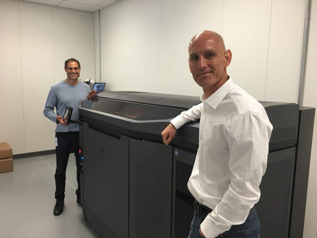 John Dulchinos (left), VP, Global Automation and 3D Printing, and Bill Muir, COO, next to the first production units of the HP MJF 3D Printer at one of Jabil's additive manufacturing labs. Photo via Jabil.