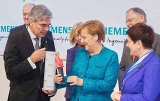 Siemens CEO Joe Kaeser hands over a 3D printed duplicate to Chancellor Angela Merkel during her visit at the Siemens booth with Polish Prime Minister Beata Szydło.