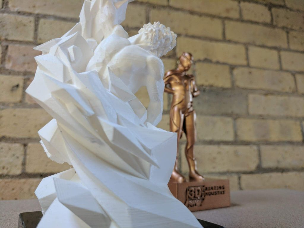 A PLA 3D print of the trophy together with another entry in the design competition. Photo by Michael Petch.