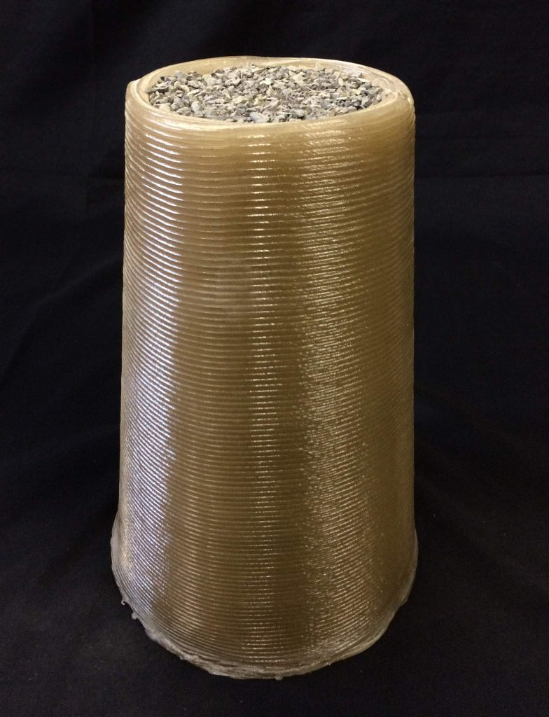The 3D printed cylinder filled with regolith-like rock. Winner of level 1, phase 2 in the NASA Centennial Challenge. Photo via Foster + Partners/Branch Technology