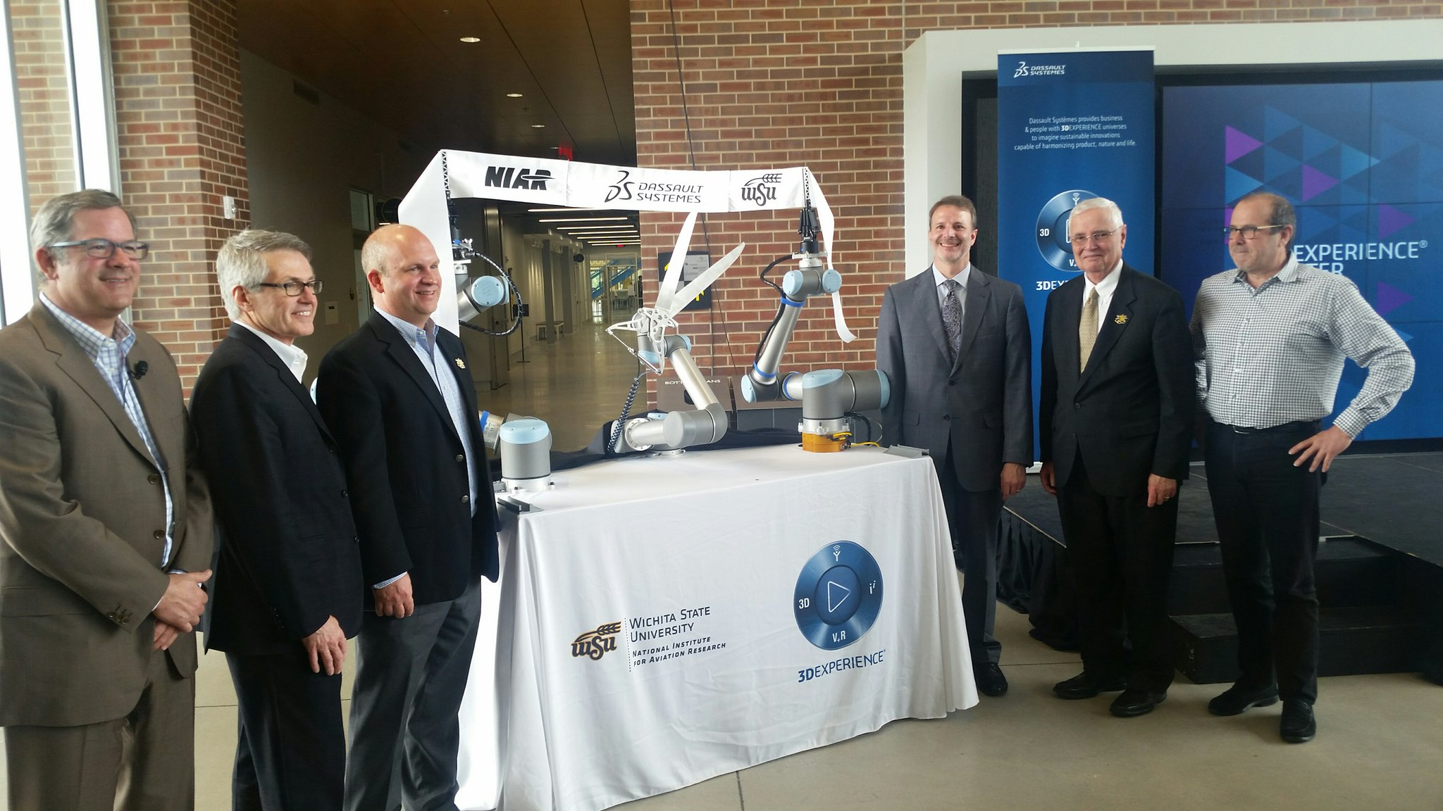 Robots were employed to both hold and cut the ribbon at Dassault's pening ceremony at WSU. Photo via U.S. Economic Development Administration.