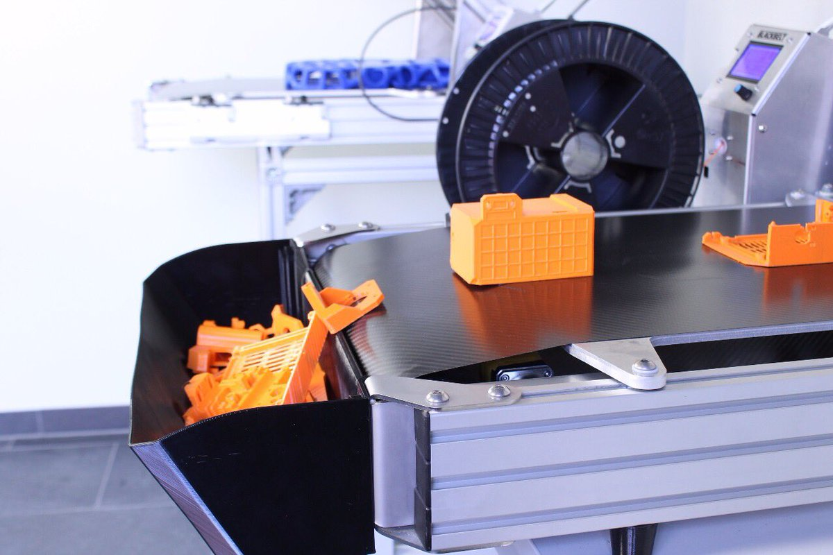 The conveyor belt features a basket to collect parts while the machine continuously prints. Photo via Blackbelt.