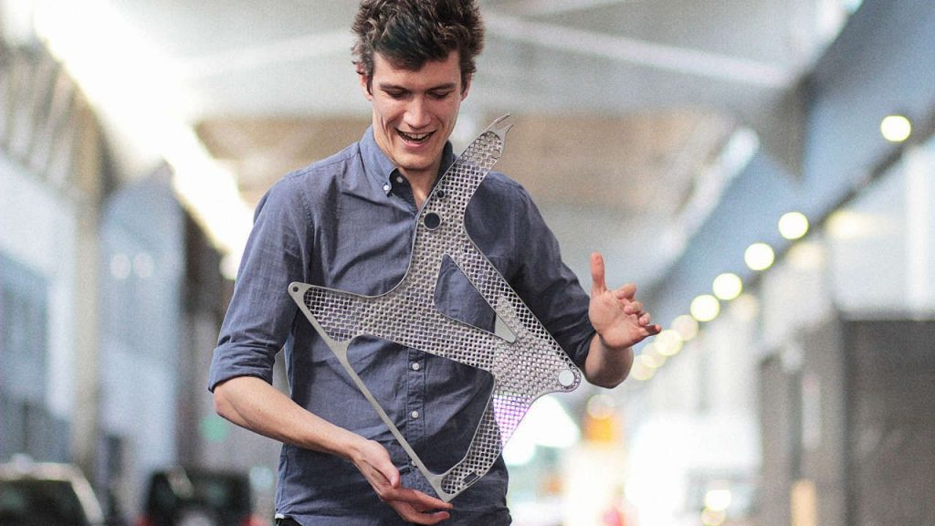Andreas Bastian shows just how light his generative design seat frame is. Photo via Autodesk.