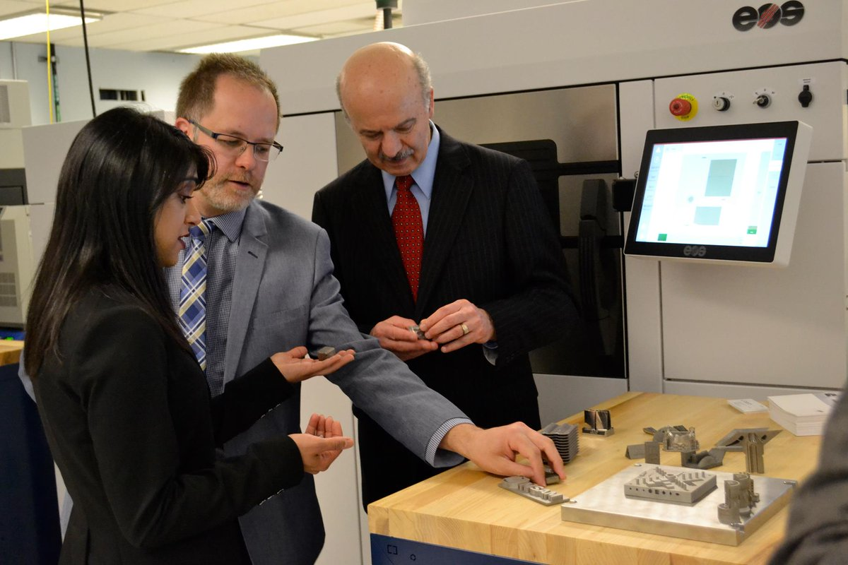 The two MPs, Chagger and Moridi, examine metal 3D printed parts. Photo via University of Waterloo.