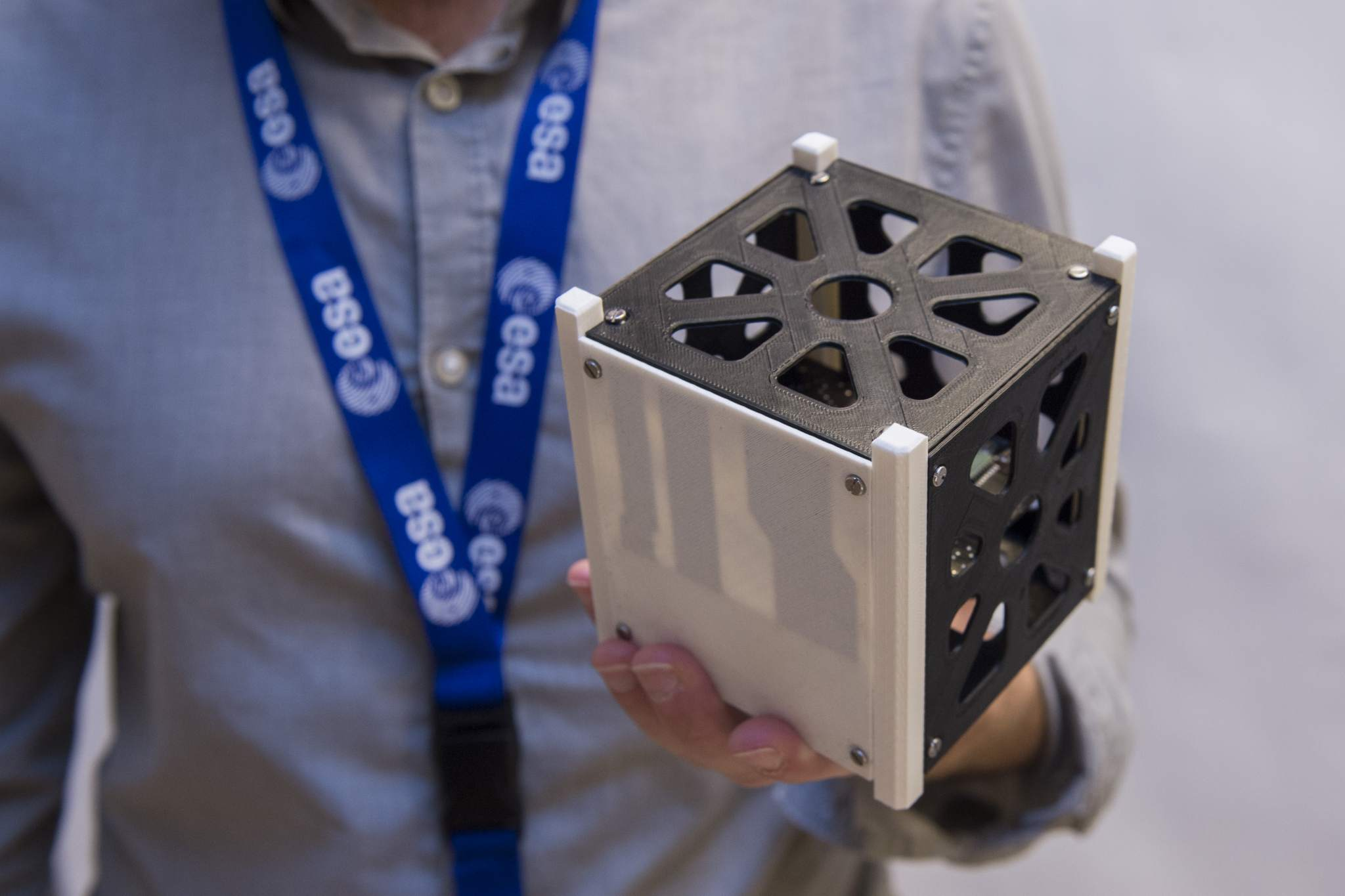 The darker electrical lines are visible through the white side of the Cube sat. Photo via ESA/Medialab.