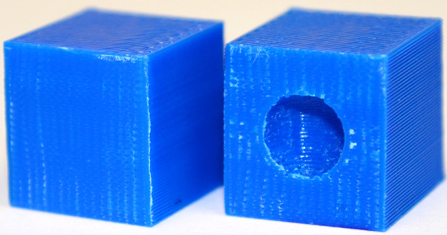 """In the CAD model on the left the deliberately embedded sphere disappears showing that the part is printed as high quality solid block when the right conditions are used. In the block on the right, the embedded sphere prints as a void if the required printing conditions are not used, giving that part lower strength."" Photo by Nikhil Gupta, Ph.D."