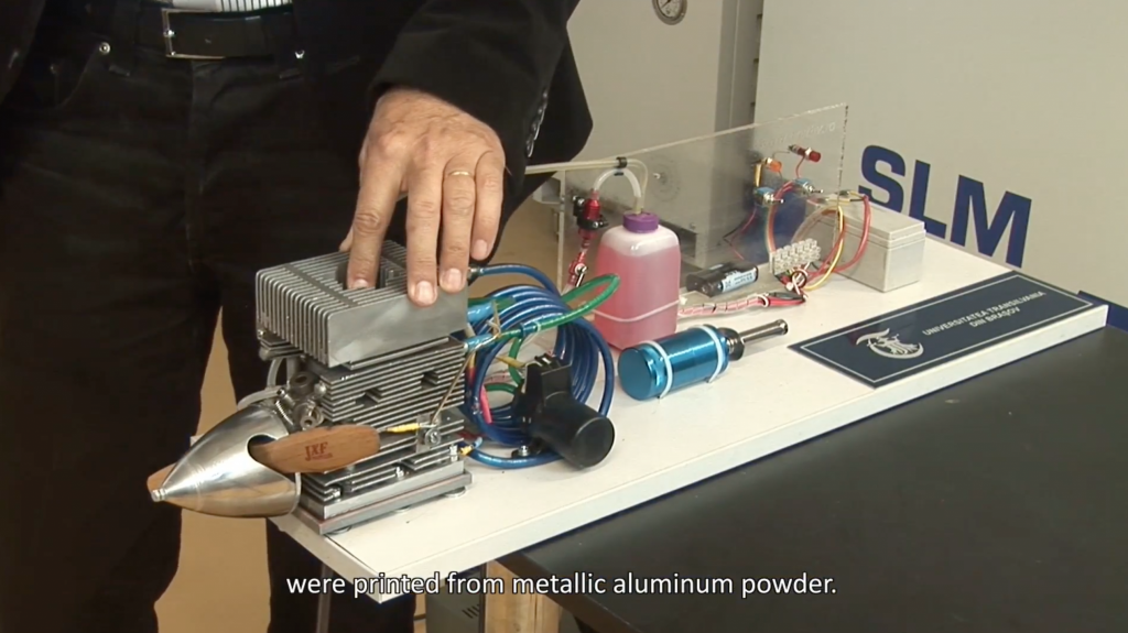 Stamate gives a walkthrough of the 3D printed parts, here showing one that is made from aluminium powder. Screenshot via Universitatea Transilvania din Brasov on YouTube