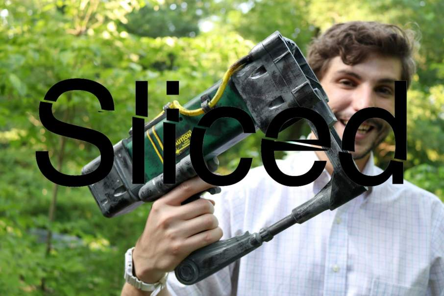 Sliced logo over Andrew Sink (3D Central) holding the 3D printed Fallout 3 laser pistol. Photo via AndrewSink on Imgur
