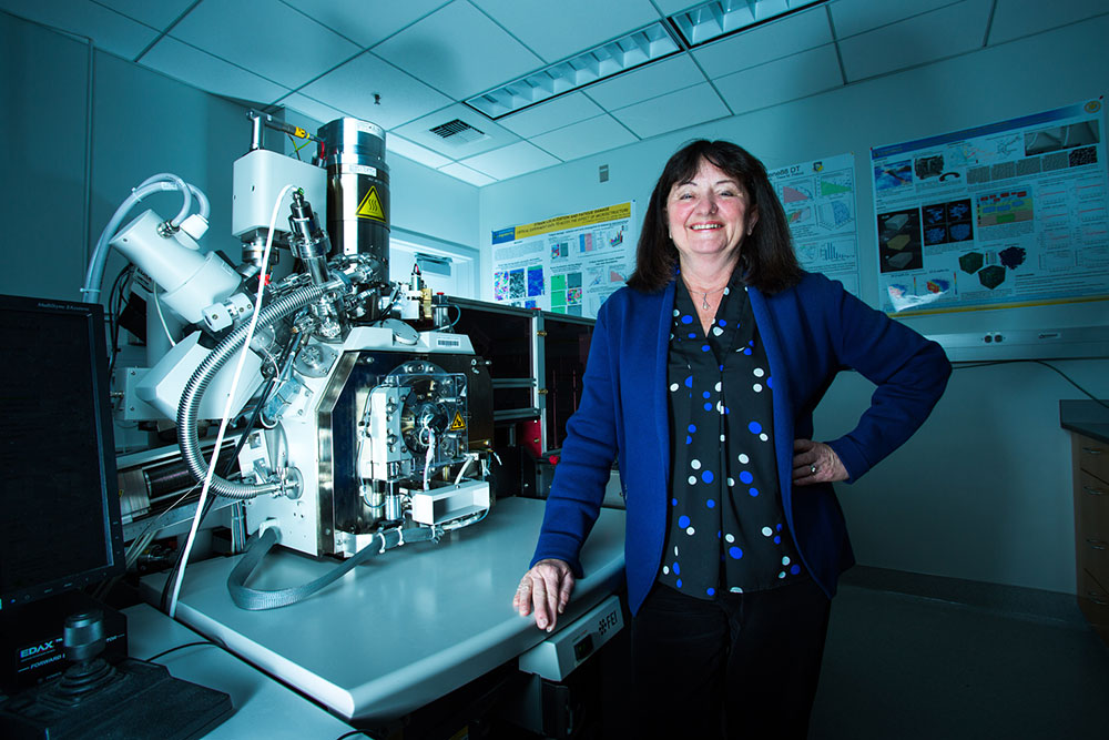 Tresa Pollock next to an electron microscope which is connected to a 3D printing chamber. Photo by Matt Perko for UC Santa Barbara.