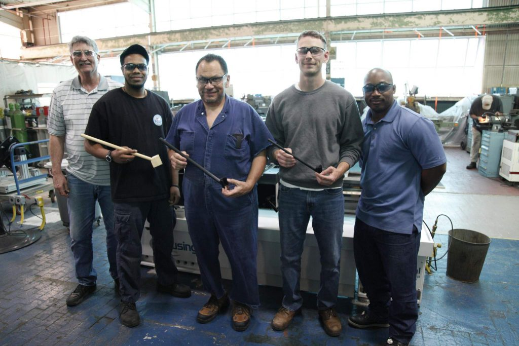 Members of the Norfolk Naval Shipyard Rapid Prototype Lab and Shop 72 (Rigging Department) Lifting and Handling Specialist Jonathan Woodruff showcase the progression of prototypes of the Tie Bolt Anti-Rotation Tool. Photo by: Kristi Britt