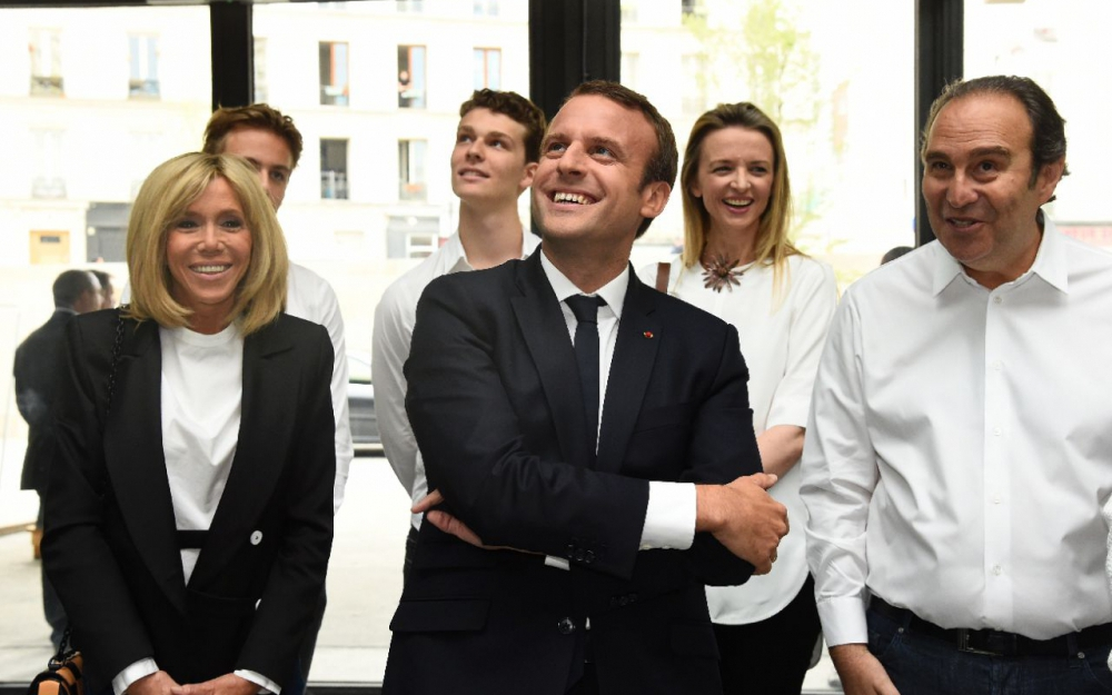 Brigitte and Emmanual Macron (left) stand with Xavier Niel (right). Photo by Bertrand Guay/AFP