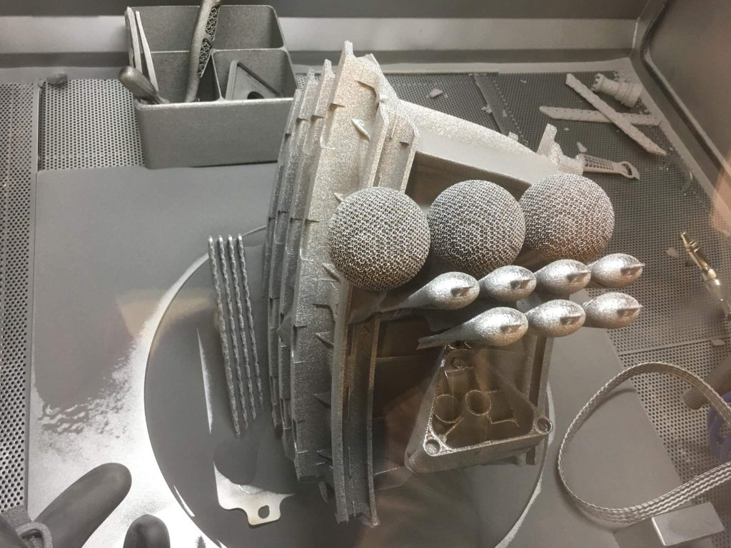Metal 3D printed parts stacked from an Arcam EBM print run.