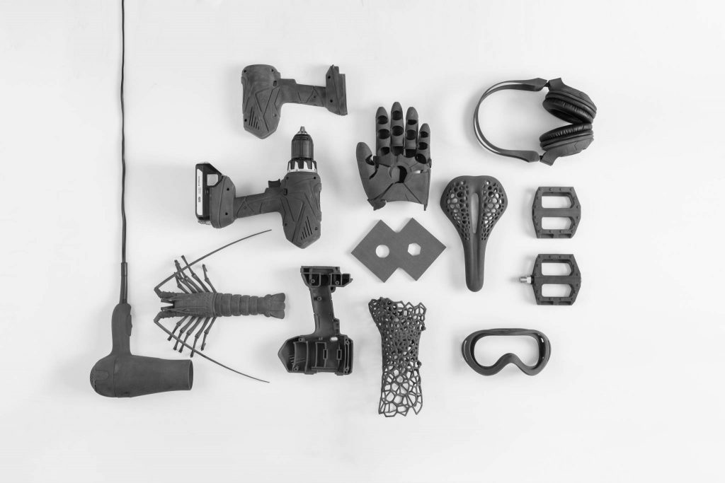 Parts 3D printed on the Fuse 1, including a drill housing, bicycle seat and headphones prototype. Photo via Formlabs