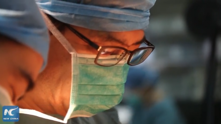 Surgeons in Xijing Hospital's operating theatre, implanting the 4D printed breast. Screenshot via New China TV on YouTube