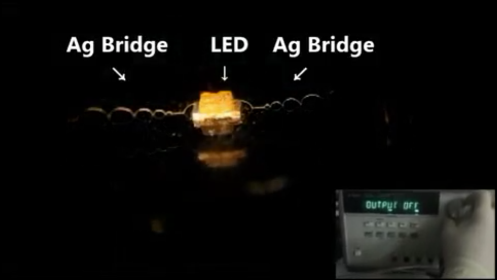 A micro LED lights up when fed an electrical charge from 3D printed silver inks. Screenshot via supplementary materials ACS Applied Materials & Interfaces.