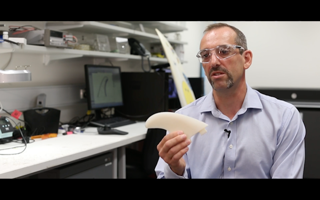 Marc in het Panhuis holds a 3D printed surfboard fin, ina video clip from the University of Wollongong. Screenshot via uownow on YouTube