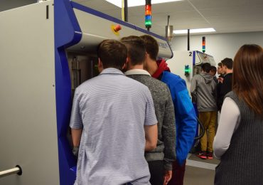 Students captivated by the laser sintering process; it's quite elegant to watch.