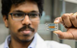 Postdoctoral researcher Karteek Kadimisetty holds the 3D printed chip of the toxicity testing device. Photo by Peter Morenus for UConn